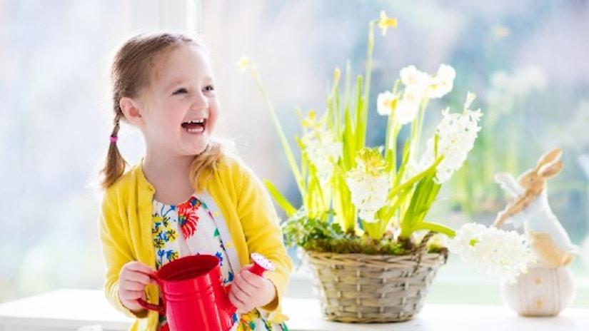 Ein kleines lachendes Mädchen mit Gießkanne