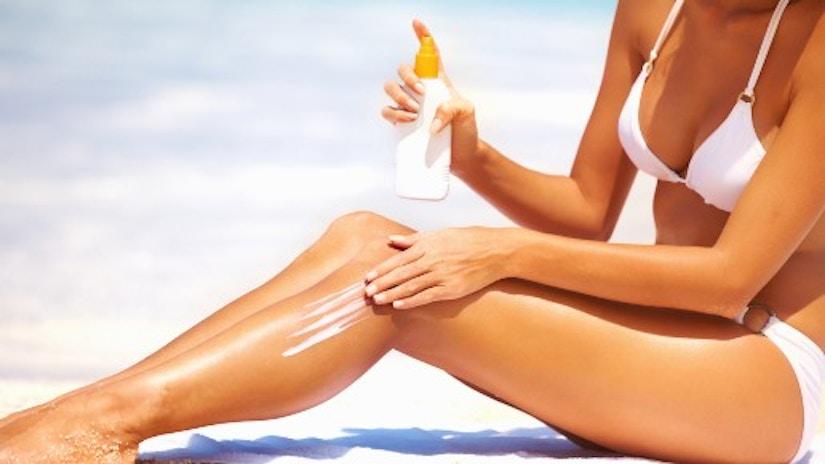 Eine Frau trägt Sonnencreme auf ihre Beine auf