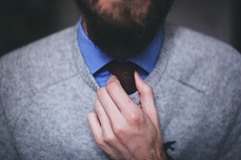 Nahaufnahme auf Mann mit Pullover über Hemd und Krawatte.