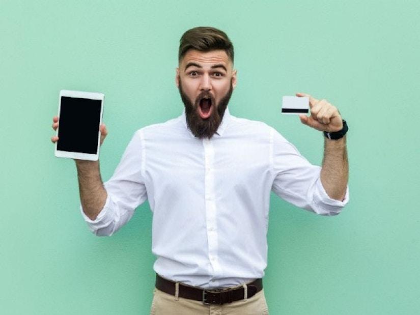 Ein Mann steht vor grünem Hintergrund und hält eine Kreditkarte sowie ein Tablet in der Hand.