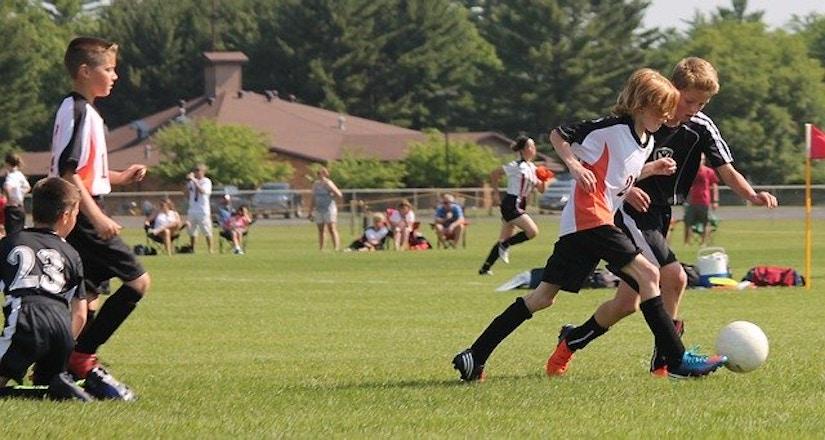 Jugendmannschaften in einheitlichen Trikots spielen Fußball