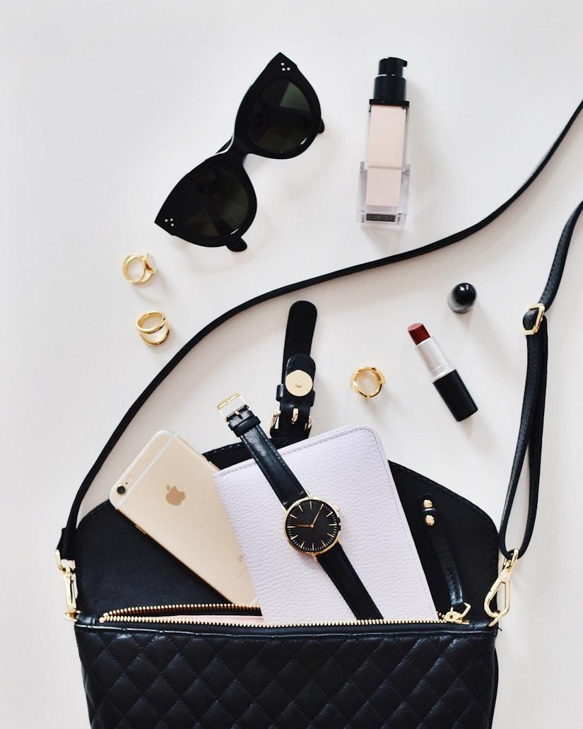Sonnenbrille, Handtasche und Kosmetika auf weißem Untergrund