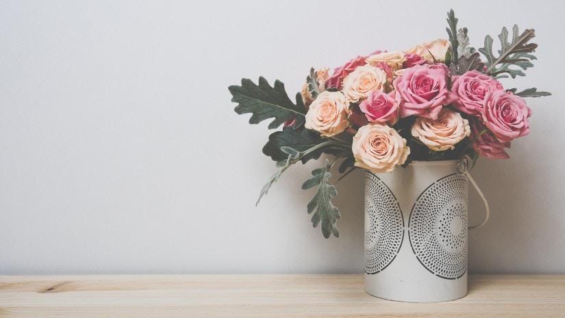 Ein Strauß rosa Rosen steht auf einem Tisch.